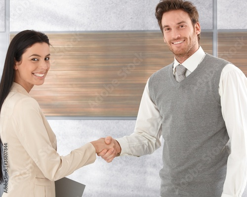 Happy business partners shaking hands