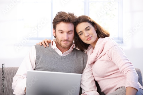 Young couple using laptop at home smiling