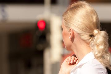 Frau steht an roter Ampel