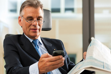 Chef in seinem Büro checkt seine Mails