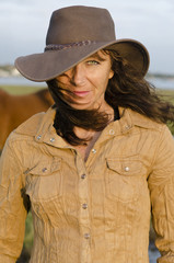 A portrait of woman wearing western hat.