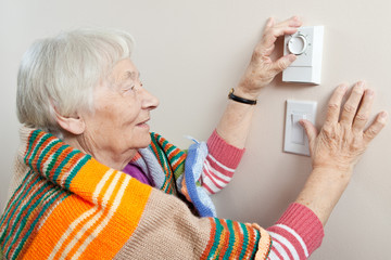 Senior woman adjusting her thermostat