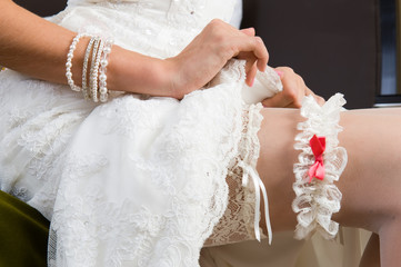 White garter, dressed on the Bride's leg.