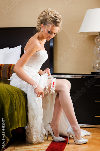 beautiful bride is trying the garter.