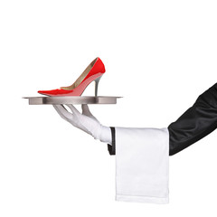 A waiter holding a silver tray with a red high heel on it