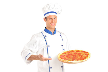 A young chef holding a pizza