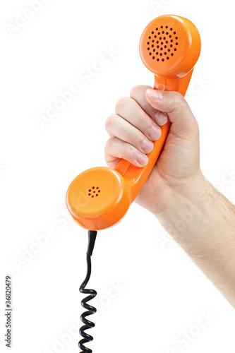 Hand holding an old orange telephone tube