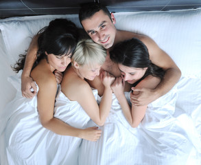 Young handsome man lying in bed with three girls
