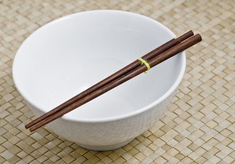 white bowl with a dark wooden chopsticks