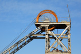 Old, disused mine shaft headgear with pulley wheel poster