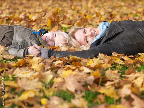 Mother and daughter enjoy autumn while lying in leaves