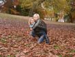Mother carring her daughter piggyback in an autumn landscape