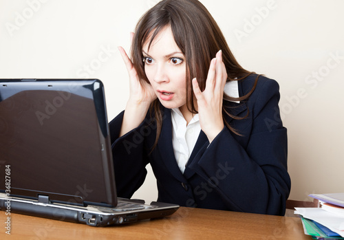 Frightened woman is looking at the laptop screen