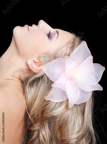 young beautiful pretty woman with flower in long blonde hair
