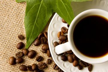 taza de café con granos tostados y hojas