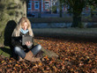 Woman sitting between autumn leaves and surfing on the internet