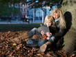 Mother and daughter back against a tree playing with touchpad