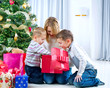 Children with Christmas gifts. Christmas tree