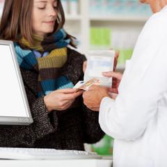 frau mit schal bezahlt ein medikament