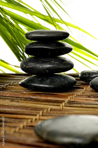 stacked pebble stones with palm leaf on bamboo mat © Mee Ting