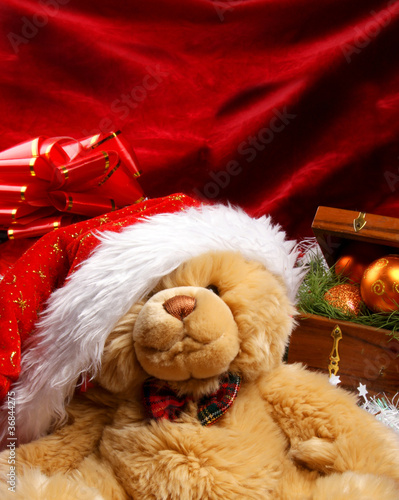 A cute teddy bear on a red Christmas background