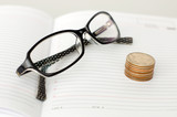 Business glasses, diary and coins