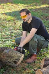 Man cutting tree trunk with electric saw