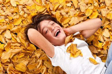 6 years kid laughing, lying on autumn leaves.