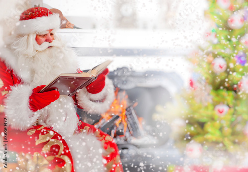 Santa sitting at the Christmas tree, near fireplace and reading