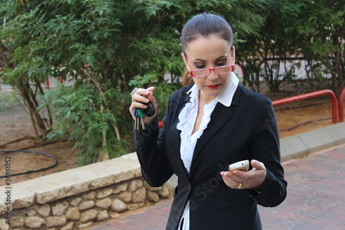 Beautiful business woman, outdoor, talks on her cell phone