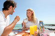 Couple having breakfast by blue lagoon