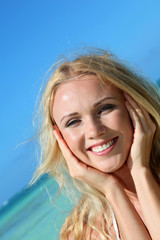 Blond woman at the beach with hands on chin