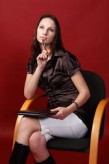 Studentin sitzt nachdenkend auf einem Stuhl
