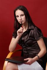 Nachdenkende Frau presst Kugelschreiber an die Lippen