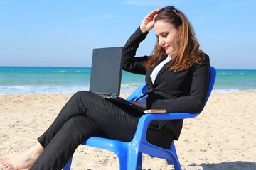 Business woman sits and works, near the ocean