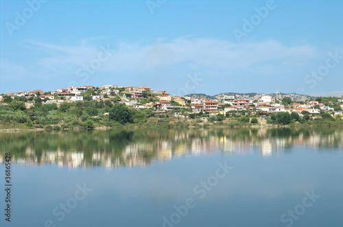 village of Mursi in Southern Albania, reflected in a man-made lake