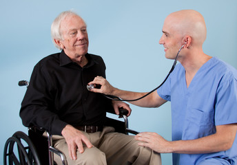 Doctor or nurse listening to elderly patients heart.
