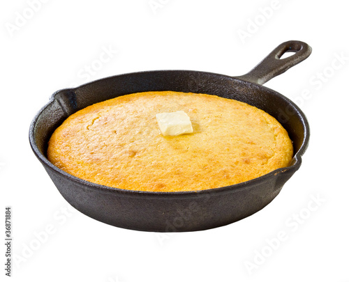 Cornbread in iron skillet isolated on white