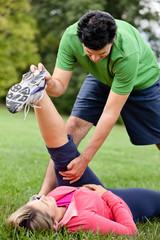 Personal trainer helping female athlete stretch leg