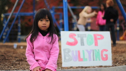 Angry Asian Girl With Stop Bullying Sign At School