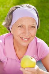 Senior sportive woman smile eat apple outdoor