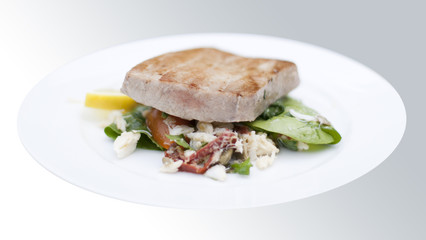 Grilled marinated Ahi tuna salad with crab, baby spinach, dressi