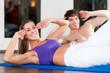 Paar macht Situps in einem Fitnessstudio