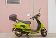 Green Scooter Against Pink Wall