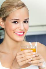 Portrait of woman with orange juice, indoors