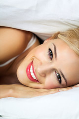 Happy smiling woman waking up at bedroom