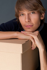 Portrait of young man leaning on box against grey wall. He is st