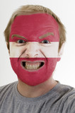 Face of crazy angry man painted in colors of latvia flag