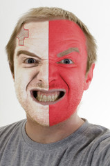 Face of crazy angry man painted in colors of malta flag