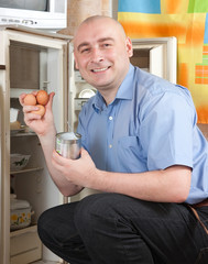 man putting with metal can near refrigerator